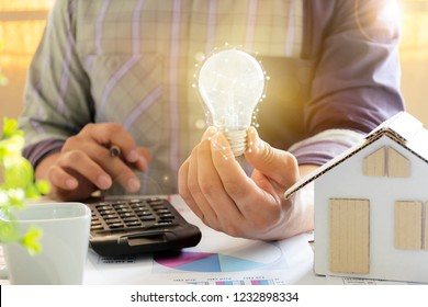 Energy concept. Men who are calculating cost savings from energy. Hand holding a light bulb, and a pencil. Home model, calculator, Chart document.
