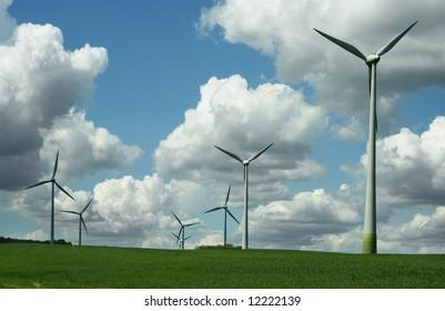 energy concept - wind turbines in beautiful summer landscape, amazing cloudscape