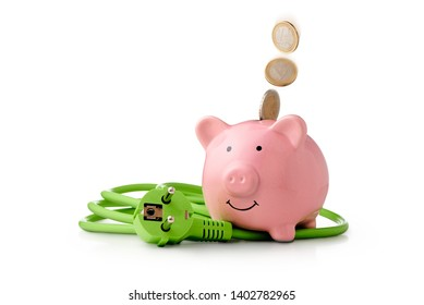 Energy costs - saving energy is good for climate protection and saves money. Euro coins fall into the piggy bank. Next to the piggy bank is a green power cord with plug