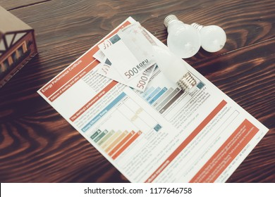 Energy Efficiency Certificate with Bulbs on Table. Classification of Energy Saving. Lightbulb on Desk. Ecology and Energy Saving Concepts. Effective Technology. Paper Certificate. Money Saving.