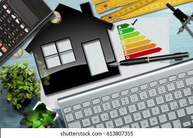 Energy efficiency rating graph on a desk with a house model, calculator, folding ruler, drawing compass, pencil and a computer keyboard