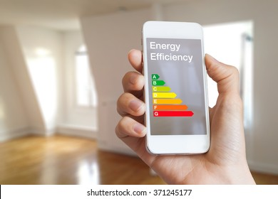Energy efficiency rating on smartphone app by woman real estate agent and home interior in background