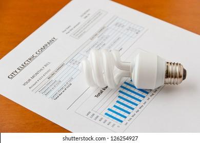 Energy efficient CFL bulb on electric bill. Energy efficient house concept.  selective focus