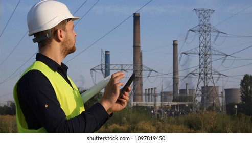 Energy Engineer Man Using Digital Tablet while Looking Up Inspecting the Power Plant Wire Lines Network