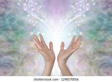 Energy flows where your attention goes - female hands reaching up towards a symmetrical shower of glittering sparkles against an ethereal pale green gold energy background