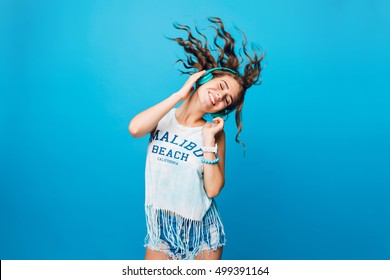 Energy girl with blue headphones  listening to music with closed eyes  on blue background in studio. She wears white T-shirt, shorts. Long curly hair in tail is flying from moving.