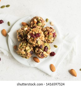 Energy granola bites with nuts, seeds, dry cranberries and honey - vegan vegetarian raw organic snack granola bites on white background, copy space.