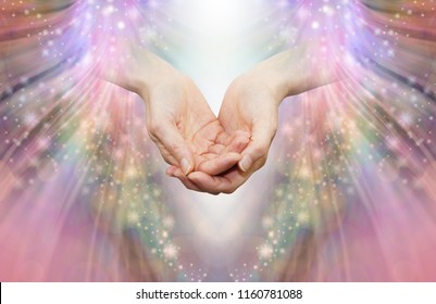 Energy healer receiving high vibrational energy - female cupped hands and shaft of white light against an angelic pink and sparkle energy flow background