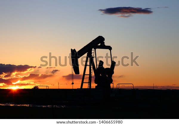 Energy industry oil pump silhouette with the sun setting with clear sky in the high plains of Texas