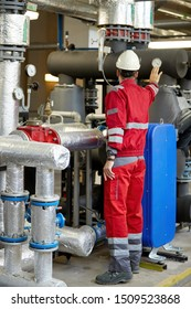 Energy industry. Technician dressed in red overalls and white helmet checking the heating parameters. Heating water distribution technology, pipes and components. Service work in power engineering.