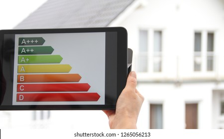 Energy label on a tablet with a house in the background