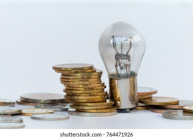 Energy light bulb on the coin stack have white background,For business design background,Defocused and Blurred