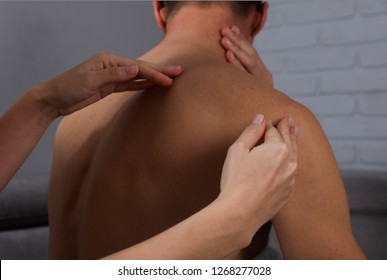 Energy massage and acupressure, holistic reiki treatment. Man having Chiropractic or Osteopathy adjustment.