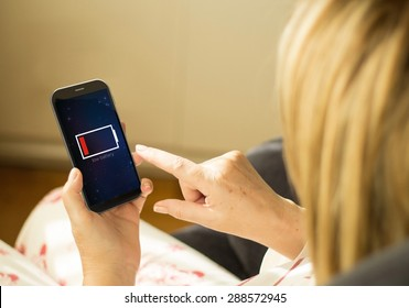 energy and modern lifestyle concept: young woman with a low battery interface on a 3d generated smartphone. All screen graphics made up.