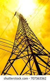 energy power concept: high voltage pylons with cloud and sun background.