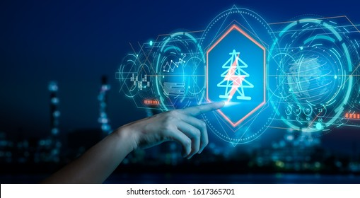 Energy and  power plant concept.Human hand holding a icon electric bolt on blurry bokeh power plant background.Industry 4.0 concept image.