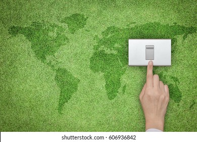 Energy saving and ecological friendly concept with hand turning off switch on grass lawn with world map
