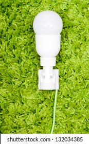 Energy saving lamp in the socket, with green wire, on the green carpet.