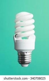 Energy saving light bulb over green background