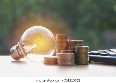 Energy saving light bulb with stacks of coins and calculator for financial, accounting and saving concept.