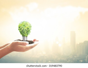Energy saving sustainable concept: Human hand holding light bulb of tree over blurred big city with world map of clouds background