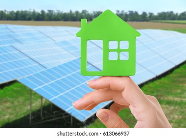 Energy savings concept. Female hand with house shaped figure on solar panels background
