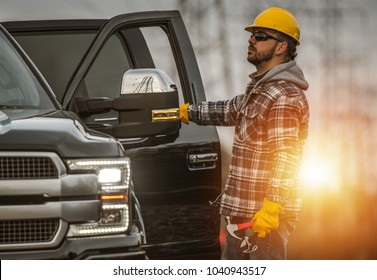 Energy Sector Worker in the Field. Electrical Infrastructure Construction Technician and His Company Truck. High Voltage Lines Maintenance.