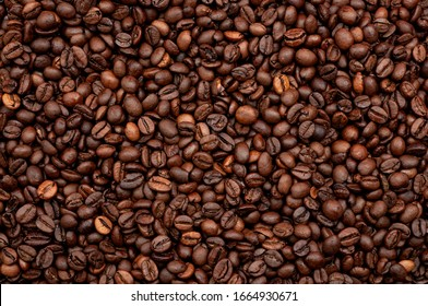 Energy stimulant and smooth java concept with full frame photograph of piled roasting coffee beans backgrounds