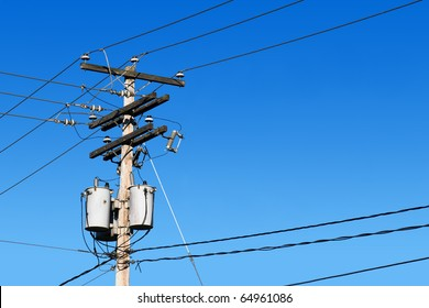 Energy and technology: electrical post by the road with power line cables, transformers and phone lines against bright blue sky providing copy space.