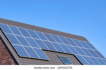 Energy, technology, electricity and ecological concept: solar panels on a house roof as a source of clean renewable energy.