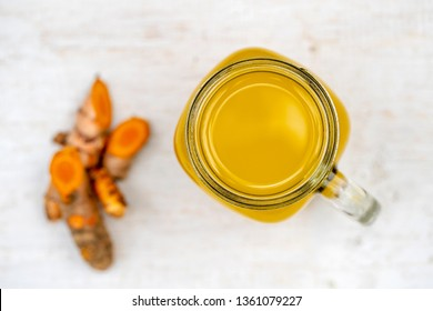 Energy tonic drink with turmeric, ginger, lemon and honey in glass mug, white wooden background, close up, top view . The concept of healthy eating