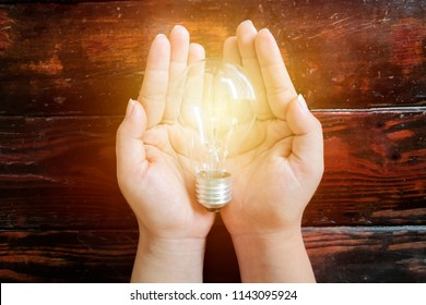 Energy-saving concept. A light bulb placed on the woman's hand. Lighting is a necessity for living.