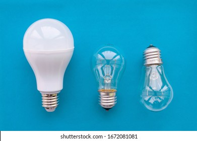 Energy-saving lamp with incandescent lamps in a row on a blue background. The concept of saving energy. Close up.