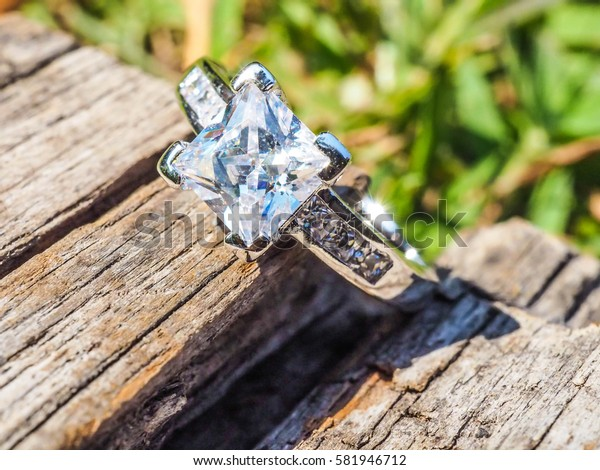An Engage Diamond ring in square shape setting with a cut diamond around on