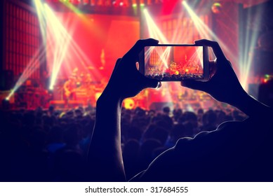 engage your audience Crowd with the power of social network by Smart phones, silhouette of a man use mobile phone camera enjoying the concert.