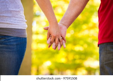 engaged couple holding hands walking