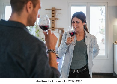 Engaged couple at a time of intimacy at home - Boyfriend and girlfriend drink a glass of red wine - Wife and husband in their new home