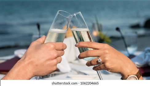 Engaged couple toasting champagne glasses at sunset on the beach