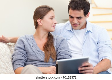 Engaged couple using a tablet computer in their living room