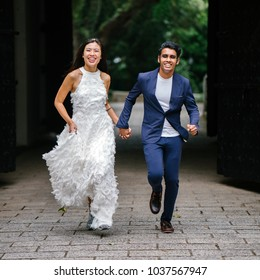 An engaged interracial Asian couple run towards the camera in a park in Singapore. An Indian man and his Chinese wife are holding hands and laughing in joy as they run.