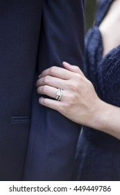 Engaged male and female hands showing off engagement ring in a romantic pose