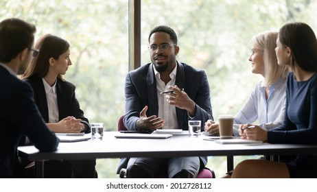 Engaged motivated African American business leader talking to team, meeting with employees, managers. Corporate coach, mentor training staff. Diverse group discussing work project at table