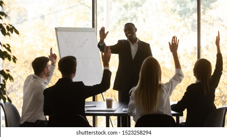 Engaged young business team raising hands, taking part in voting, making unanimous decision at brainstorming meeting in office. Motivated group supporting new project of african american leader.