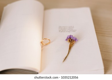 An engagement ring on the background of a book and a flower. Proposal of marriage. Wedding details.