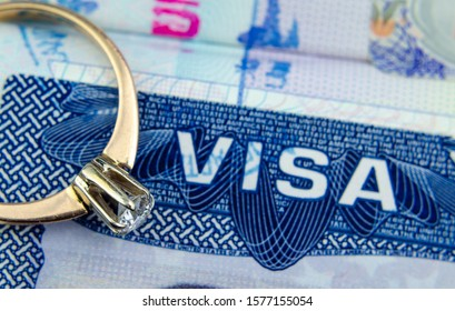 Engagement ring on top of blurred US entry visa sticker in a passport. Conceptual photo for fiance visa and immigration in general. Selective focus.