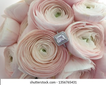 Engagement ring in a pale pink flower bouquet
