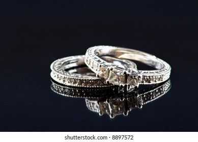 Engagement ring and wedding band on black background with reflection