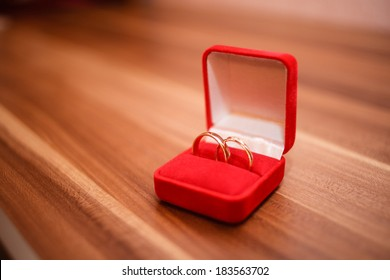 Engagement rings in red box on table.
