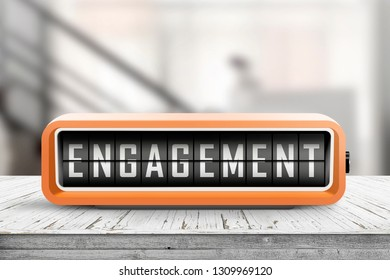 Engagement text on an orange alarm clock on a table in a hall