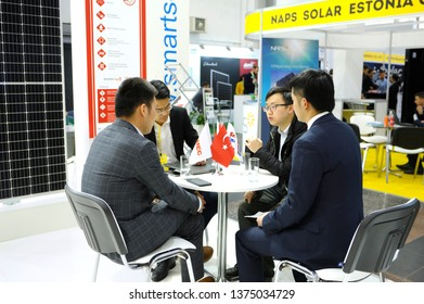Engaging in dialogue. Asian businessmen sitting at the table at the stand zone and negotiating during an exhibition Solar Energy Trade Show. April 19, 2019.Kiev, Ukraine